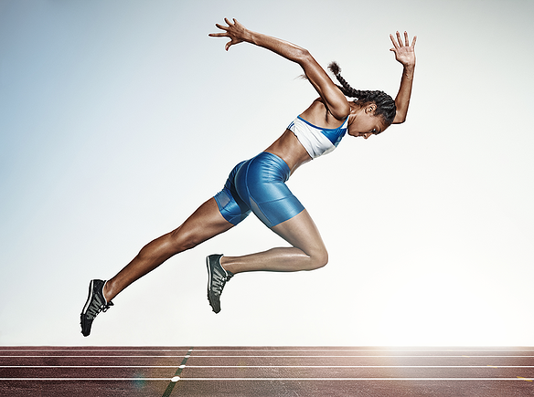 Woman in running form about to take off running on an outdoor track.