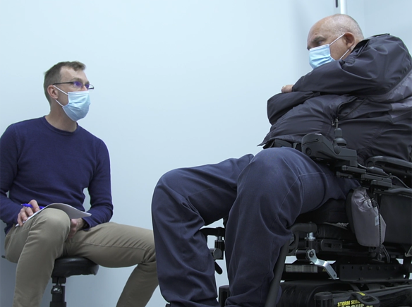 Occupational Therapist Timothy Hill discusses strategy with his wheelchair-bound patient.