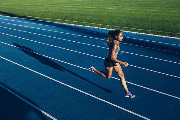 Woman running on an outdoor track.